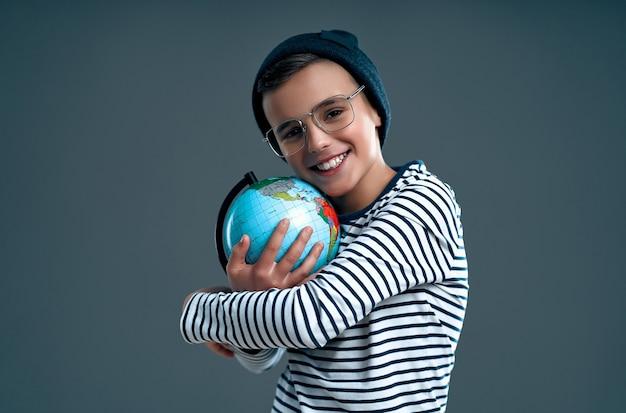 Élégant écolier d'enfant intelligent dans un chapeau et des lunettes embrasse un globe isolé sur un gris.