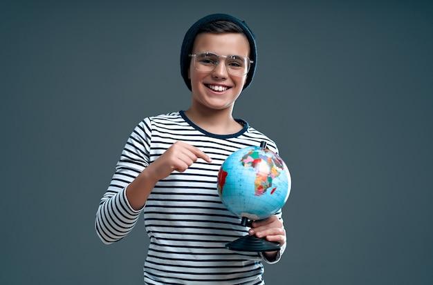Élégant écolier d'enfant intelligent dans un chapeau et des lunettes montre un doigt sur un globe isolé sur un gris.
