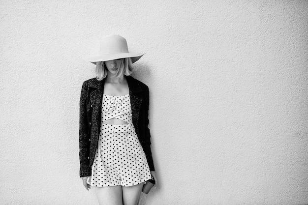 Élégant élégant chapeau de femme blonde cheveux courts et robe posant avec café