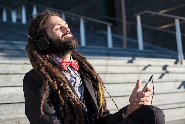 Élégant élégant dreadlocks homme d'affaires écoute musique