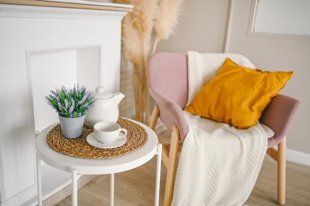 Élégant élégant salon de composition écologique avec table de petit-déjeuner blanche tasse à café théière fausse cheminée fleurs séchées plantes pampa herbe fauteuil en poudre rose, couverture et oreiller