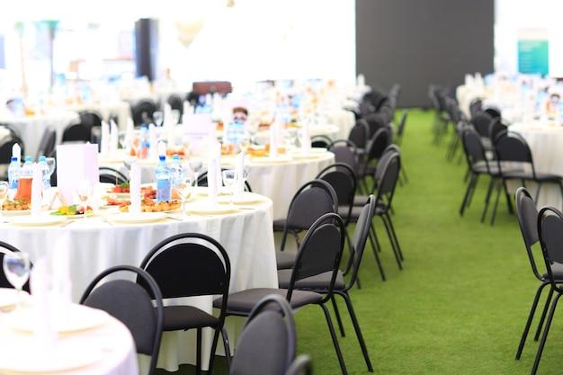 Élégant espace de réception de mariage, prêt pour les invités et la noce. table riche en bouquet de fleurs.