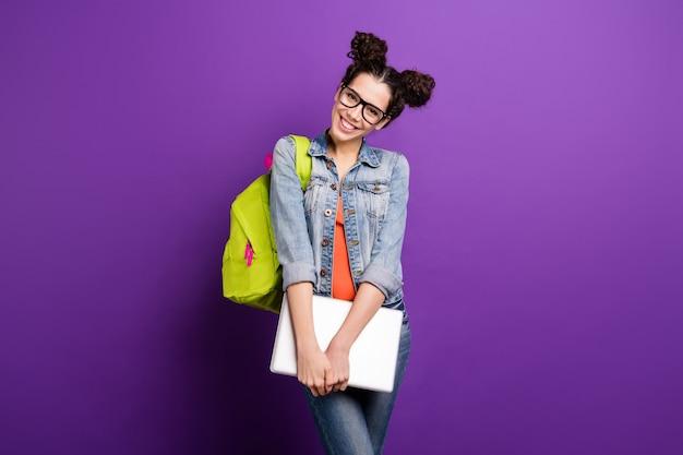 Élégant étudiant aux cheveux bouclés posant contre le mur violet