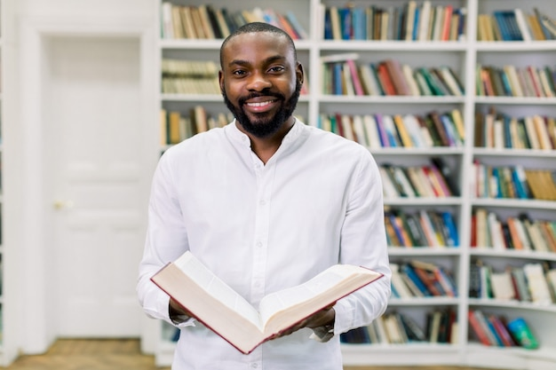 Élégant étudiant à la peau sombre en chemise blanche, lecture de livre en se tenant dans la bibliothèque contre les étagères.