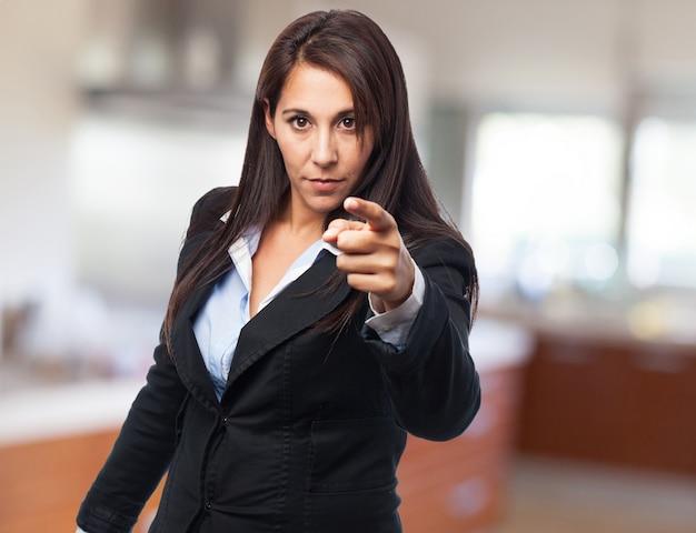 Élégant femme sérieuse pointant vers l'avant