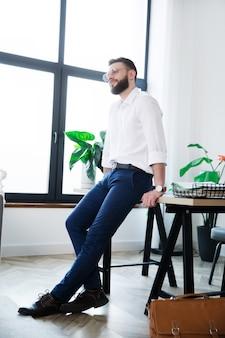 Élégant homme d'affaires moderne heureux dans des vêtements décontractés intelligents pose dans le bureau de démarrage pendant la pause-café