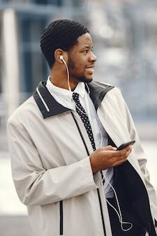 Élégant homme afro-américain debout dans la rue à l'aide d'un téléphone mobile avec des écouteurs.