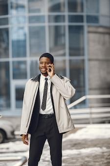 Élégant homme afro-américain debout dans la rue, parler sur un téléphone mobile.