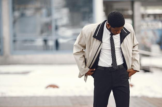 Élégant homme afro-américain debout dans la rue.
