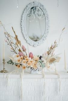 Élégant intérieur de maison dans des tons blancs avec miroir vintage sous la cheminée décoré d'une belle composition de fleurs séchées.