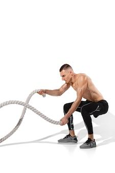 Élégant jeune athlète masculin pratiquant sur fond de studio blanc, portrait avec des ombres. modèle de coupe sportive en mouvement et en action.