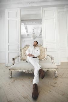 Élégant jeune bel homme avec une barbe dans un costume classique blanc. l'intérieur de l'hôtel. studio de photographie. sofa. fenêtre. chaise. lustre