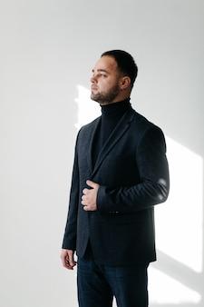 Élégant jeune bel homme en costume noir classique. portrait de mode en studio.