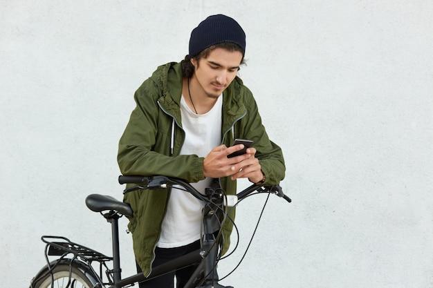 Élégant jeune en chapeau noir et veste avec capuche, a un style de vie actif, couvre de longues distances avec son vélo de sport, a une pause