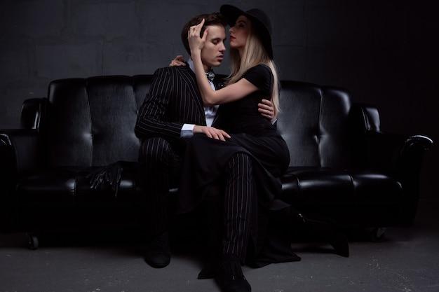 Un élégant jeune couple amoureux embrasse dans une tendre passion assis sur un canapé en cuir noir