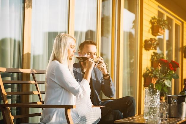 Élégant jeune couple assis dans le patio, boire du vin rouge