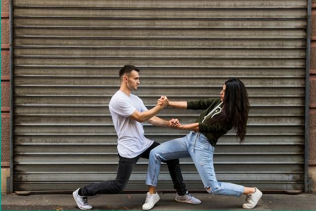 Élégant jeune couple dansant devant le mur ondulé