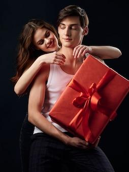 Élégant jeune couple homme et femme, il a une grande boîte cadeau