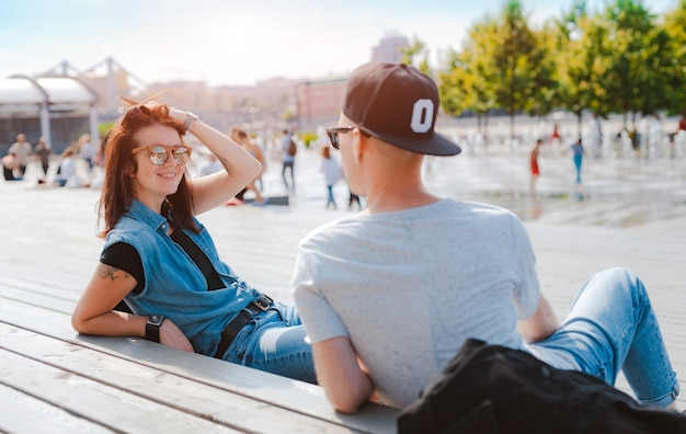 Élégant jeune couple s'amuse à discuter dans un parc de la ville en été au coucher du soleil. une fille rit lors d'une rencontre avec un petit ami.