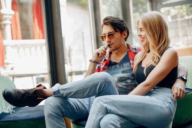 Élégant jeune couple avec vape dans un café