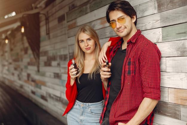 Élégant jeune couple avec vape dans une ville