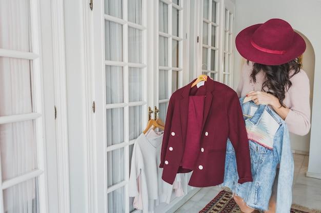 Élégant jeune femme regardant un costume bordeaux