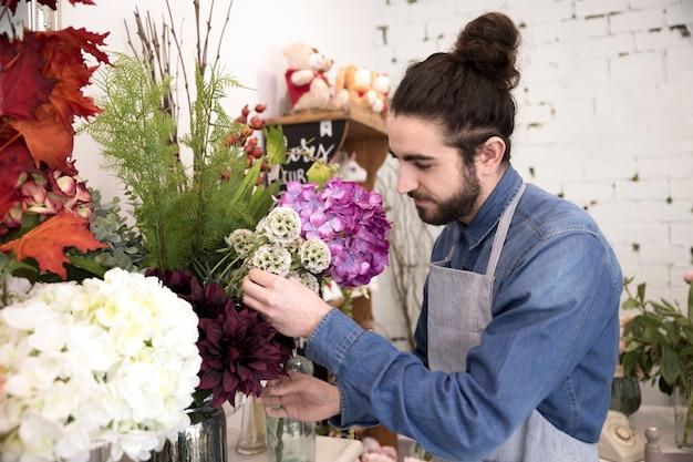 Élégant jeune fleuriste mâle arrangeant les fleurs dans le bouquet