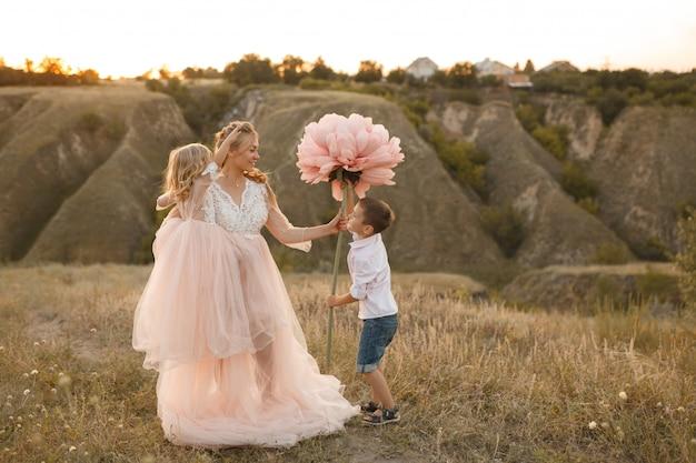 Élégant jeune garçon donne une grosse fleur à sa maman dans un champ au coucher du soleil
