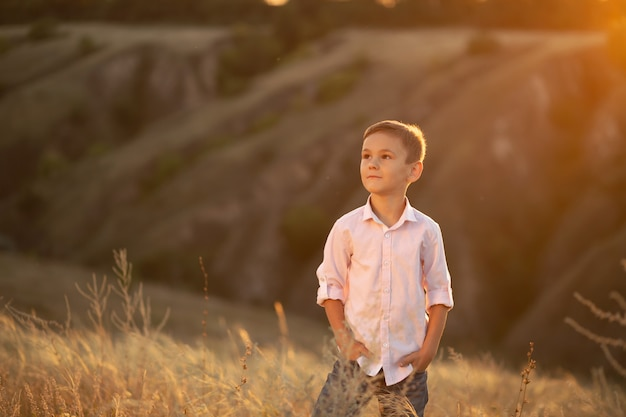 Élégant jeune garçon posant dans le champ au coucher du soleil