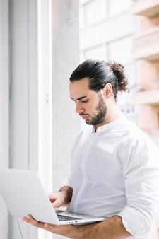 Élégant jeune homme d'affaires à l'aide d'un ordinateur portable