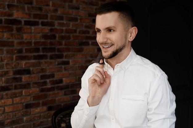 Élégant jeune homme d'affaires en chemise blanche sourit et tient une veste sur le doigt