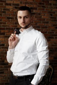 Élégant jeune homme d'affaires en chemise blanche tient une veste sur le doigt