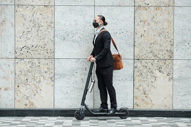 Élégant jeune homme d'affaires avec queue de cheval à cheval sur un scooter le long d'un mur de granit élevé