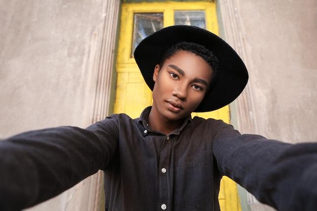 Élégant jeune homme afro-américain prenant selfie à l'extérieur