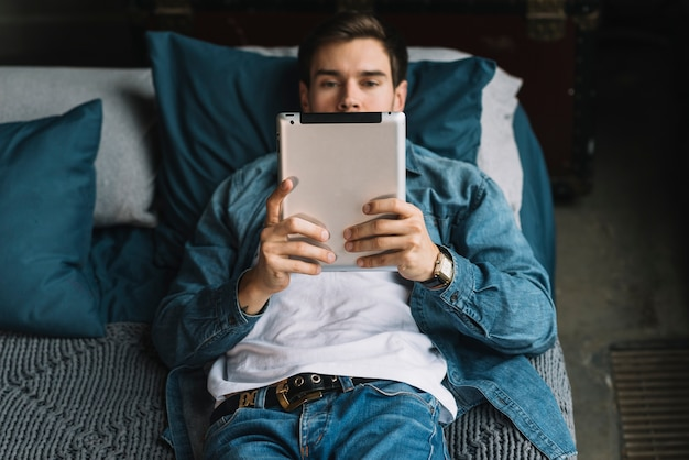 Élégant jeune homme allongé sur le lit en regardant une tablette numérique