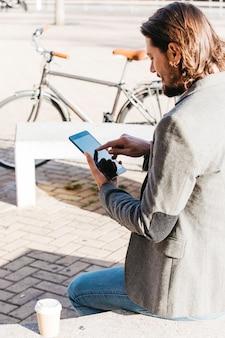 élégant jeune homme assis sur un banc avec une tasse de café à emporter à l'aide de téléphone portable