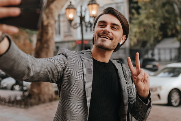 Élégant jeune homme aux cheveux noirs en chemise noire et blazer gris tendance, tenant un téléphone et faisant un selfie contre le mur de la ville d'automne