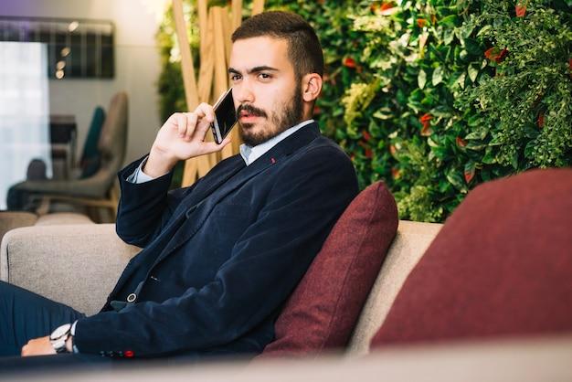 Élégant jeune homme ayant des conversations téléphoniques