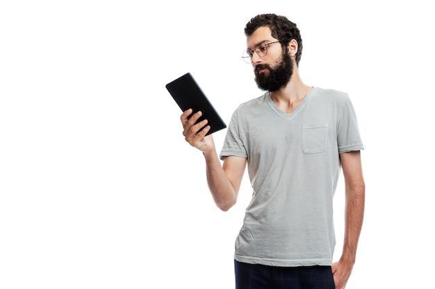 Élégant jeune homme avec une barbe et des lunettes avec une tablette à la main. formation, communication en ligne, réseaux sociaux et blogs.