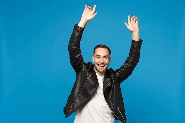 Élégant jeune homme barbu heureux en t-shirt blanc avec veste en cuir noir faisant le geste du gagnant dire oui isolé sur fond de mur bleu portrait en studio. concept d'émotions sincères de personnes. maquette de l'espace de copie