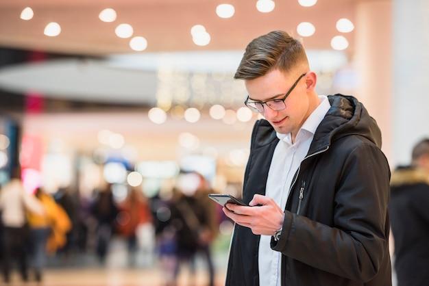 Élégant, jeune homme, centre commercial, utilisation, téléphone portable