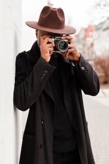 Élégant jeune homme avec un chapeau en prenant une photo