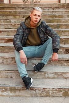 Élégant jeune homme dans une veste militaire avec un sweat à capuche et un jean posant sur les marches