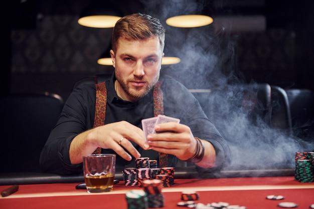 Élégant jeune homme est assis dans un casino avec de la fumée et joue au poker