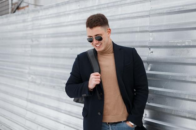 Élégant jeune homme hipster à lunettes de soleil dans un manteau élégant en jeans dans un pull tricoté à la mode avec un sac à dos est debout et souriant près de la clôture métallique
