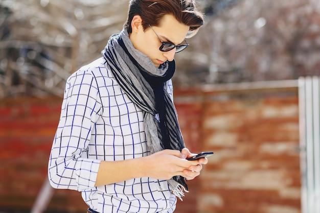 élégant jeune homme à lunettes de soleil avec téléphone sur rue