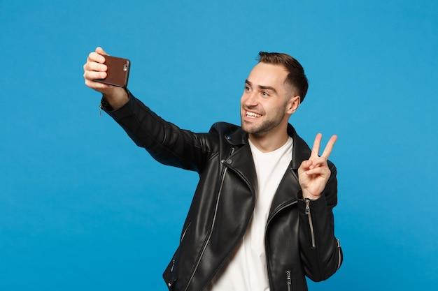 Élégant jeune homme mal rasé en t-shirt blanc veste noire oing selfie tourné sur téléphone mobile isolé sur fond de mur bleu portrait en studio. concept de mode de vie des émotions sincères des gens mock up copy space