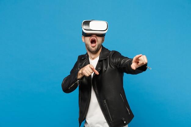 Élégant jeune homme mal rasé en t-shirt blanc veste noire regardant dans un casque, réalité virtuelle vr isolé sur fond de mur bleu portrait en studio. concept de mode de vie des émotions des gens. maquette de l'espace de copie.