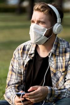 Élégant jeune homme avec masque facial, écouter de la musique