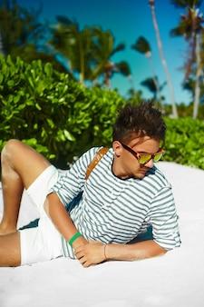 Élégant jeune homme modèle masculin allongé sur le sable de la plage portant un chapeau d'été hipster